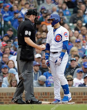 Javier Baez, Chris Conroy. Chicago Cubs' Javier Baez, right, talks with home plate umpire Chris Conroy after being called out on strikes during the third inning of a baseball game against the Cincinnati Reds, in Chicago