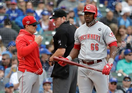 David Bell, Chris Conroy. Cincinnati Reds manager David Bell, left, talks with home plate umpire Chris Conroy, center, after Yasiel Puig, right, was struck out swinging during the second inning of a baseball game against the Chicago Cubs, in Chicago