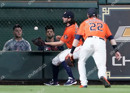 Houston Astros center fielder Jake Marisnick, left, fields a doubly by Boston Red Sox's Mookie Betts as right fielder Josh Reddick (22) watches during the fourth inning of a baseball game, in Houston