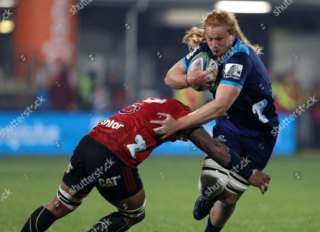 Blues Tom Robinson runs at the Crusaders Whetukamokamo Douglas during their Super Rugby match in Christchurch, New Zealand