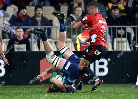 Blues Tom Robinson falls as he catches the ball as Crusaders Bryn Hall watches during their Super Rugby match in Christchurch, New Zealand