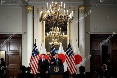 President Donald Trump speaks with Japanese business leaders, in Tokyo, as U.S. Ambassador to Japan William Hagerty listens