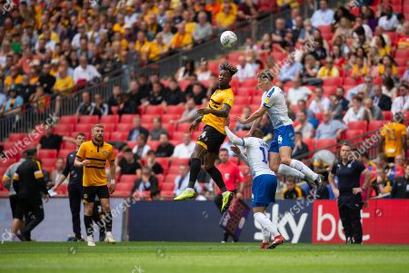 Adebayo Azeez of Newport County wins a header over Sid Nelson of Tranmere Rovers and Jake Caprice of Tranmere Rovers