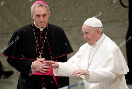 Prefect of the Papal Household Archbishop Georg Gaenswein, left, looks at Pope Francis as he arrives for an audience with participants of a pilgrimage of the Italian-Albanian diocese of Lungro, in the Pope Paul VI hall, at the Vatican
