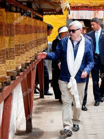 Stock Photo of And released by the U.S. Embassy in Beijing, U.S. Ambassador to China Terry Branstad rotates prayer wheels in Lhasa in western China's Tibet Autonomous Region. The U.S. ambassador to China urged Beijing to engage in substantive dialogue with exiled Tibetan Buddhist leader the Dalai Lama during a visit to the Himalayan region over the past week, the Embassy said Saturday