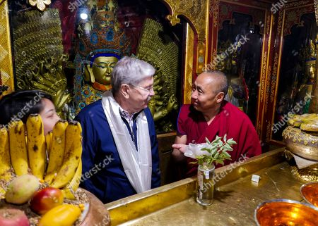 And released by the U.S. Embassy in Beijing, U.S. Ambassador to China Terry Branstad, left, speaks with a monk at the Jokhang Temple in Lhasa in western China's Tibet Autonomous Region. The U.S. ambassador to China urged Beijing to engage in substantive dialogue with exiled Tibetan Buddhist leader the Dalai Lama during a visit to the Himalayan region over the past week, the Embassy said Saturday