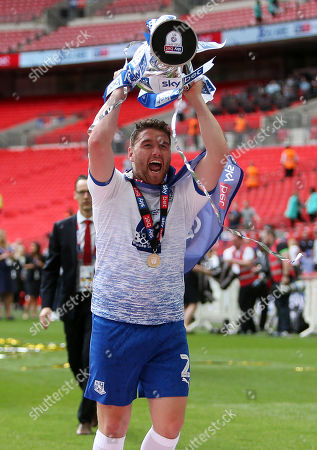 Adam Buxton of Tranmere Rovers celebrates with the trophy in front of the fans.
