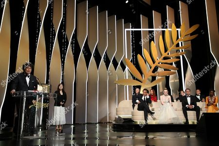 Bong Joon-ho, Robin Campillo, Alice Rohrwacher, Kelly Reichardt, Enki Bilal, Alejandro Gonzalez Inarritu, Elle Fanning, Pawel Pawlikowski, Maimouna N'Diaye. Director Bong Joon-ho, left, accepts the Palme d'Or award for the film 'Parasite' as members of the jury Robin Campillo, from back right Alice Rohrwacher, Kelly Reichardt, Enki Bilal, jury president Alejandro Gonzalez Inarritu, from bottom right, jury members Elle Fanning, Pawel Pawlikowski and Maimouna N'Diaye look on during the awards ceremony at the 72nd international film festival, Cannes, southern France