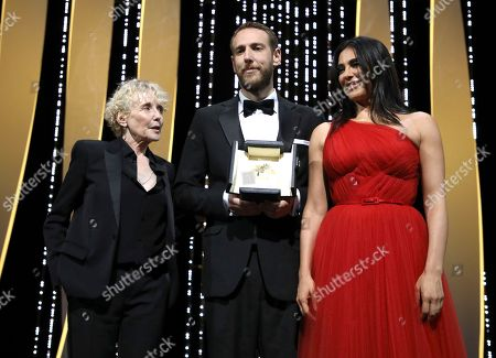 Vasilis Kekatos, Nadine Labaki, Claire Denis. Director Vasilis Kekatos, centre, receives the Palme d'Or for best short film for 'The Distance Between Us and the Sky' awarded by director Claire Denis, left, and Nadine Labaki, RIGHT, during the awards ceremony at the 72nd international film festival, Cannes, southern France