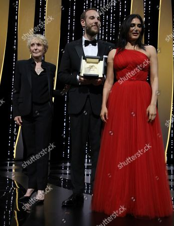 Stock Image of Vasilis Kekatos, Nadine Labaki, Claire Denis. Director Vasilis Kekatos, centre, receives the Palme d'Or for best short film for 'The Distance Between Us and the Sky' awarded by director Claire Denis, left, and Nadine Labaki, right, during the awards ceremony at the 72nd international film festival, Cannes, southern France