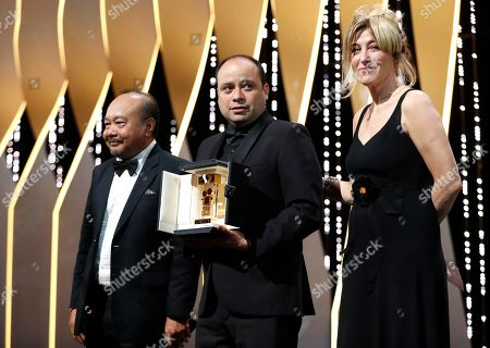 Stock Photo of Guatemalan director Cesar Diaz (C) holds his the Camera d'Or Jury Prize for the movie 'Our Mothers (Nuestra Madres)' onstage next to Camera D'or JuryPresident, Cambodian-French director Rithy Panh (L) and French actress and director Valeria Bruni Tedeschi during the Closing Awards Ceremony of the 72nd Cannes Film Festival, in Cannes, France, 25 May 2019. The Golden Palm winning movie will be screened after the closing ceremony.