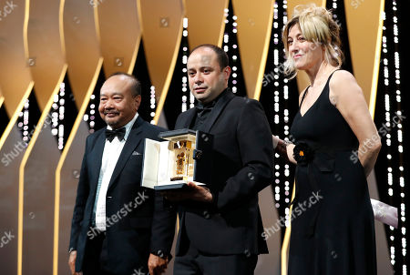 Guatemalan director Cesar Diaz (C) holds his the Camera d'Or Jury Prize for the movie 'Our Mothers (Nuestra Madres)' onstage next to Camera D'or JuryPresident, Cambodian-French director Rithy Panh (L) and French actress and director Valeria Bruni Tedeschi during the Closing Awards Ceremony of the 72nd Cannes Film Festival, in Cannes, France, 25 May 2019. The Golden Palm winning movie will be screened after the closing ceremony.