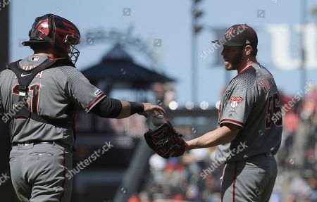 Arizona Diamondbacks catcher Alex Avila (31) celebrates with relief pitcher Greg Holland after defeating the San Francisco Giants in a baseball game in San Francisco