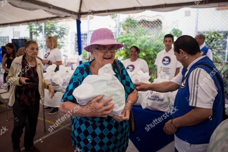 People receive humanitarian aid in Caracas, Venezuela, on 25 May 2019. Rescate Venezuela, promoted by Venezuelan opposition leader Leopoldo Lopez and his wife Lilian Tintori, delivered on 25 May basic hygiene products packages to more than 500 families in Caracas as part of their plan to distribute aid.