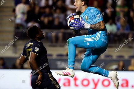 Steve Clark, Sergio Santos. Portland Timbers goalkeeper Steve Clark, right, stops the ball as Philadelphia Union's Sergio Santos runs by during the second half of an MLS soccer match in Chester, Pa