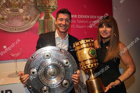 Robert Lewandowski (R) and his wife Anna Lewandowska (R) pose with the DFB Cup and Bundesliga Championship trophies during the FC Bayern Muenchen DFB Cup final's night 2019 at Deutsche Telekom's representative office in Berlin, Germany, 26 May 2019.