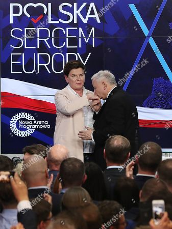 """Jaroslaw Kaczynski, Beata Szydlo. Leader of the Polish Law and Justice (PiS) ruling party Jaroslaw Kaczynski and deputy Prime Minister Beata Szydlo, left, reacts after the announcement of the exit polls of the European elections in Warsaw, Poland, .The poster on the wall reads """"Poland heart of Europe"""