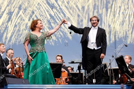 Opera singer Nina Stemme (L) and Conductor Marco Armiliato (R) greet the audience onstage during a concert outside the opera house in Vienna, Austria, 26 May 2019. The Jubilee concert outside the opera is free for all and features ensemble singers, international guest artists, the orchestra and chorus of the Wiener Staatsoper under conductor Marco Armiliato.