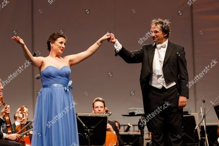 Ukrainian soprano Olga Bezsmertna (L) and Conductor Marco Armiliato (R) greet the audience onstage during a concert outside the opera house in Vienna, Austria, 26 May 2019. The Jubilee concert outside the opera is free for all and features ensemble singers, international guest artists, the orchestra and chorus of the Wiener Staatsoper under conductor Marco Armiliato.