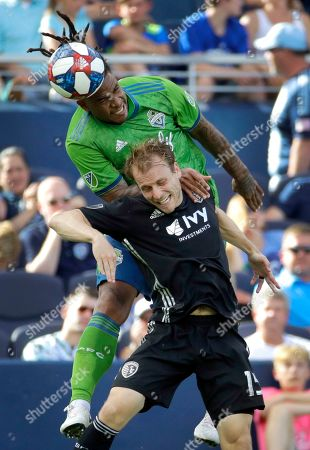 Seattle Sounders defender Roman Torres, top, and Sporting Kansas City defender Seth Sinovic battle for control of the ball during the first half of an MLS soccer match, in Kansas City, Kan