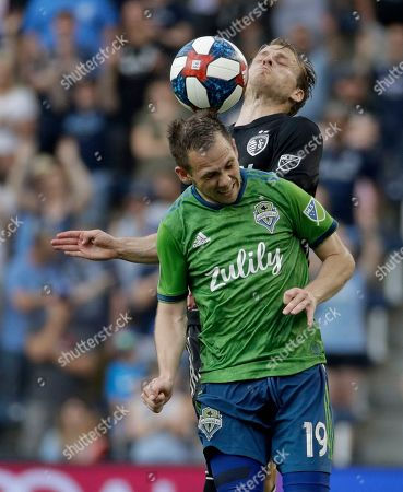 Seattle Sounders forward Harrison Shipp (19) and Sporting Kansas City defender Seth Sinovic, top, battle to control the ball during the second half of an MLS soccer match, in Kansas City, Kan