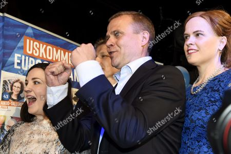 Sanni Grahn-Laasonen, chairman Petteri Orpo and Mari-Leena Talvitie react