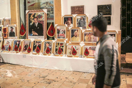 A man walks past a shop selling portraits of King Mohamed VI of Morocco and the royal family, in Rabat, Morocco