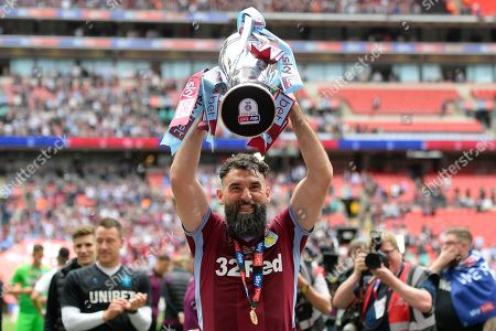 Aston Villa midfielder Mile Jedinak (15) lifts the cup during the EFL Sky Bet Championship play off final match between Aston Villa and Derby County at Wembley Stadium, London