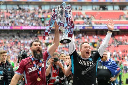 Aston Villa midfielder Mile Jedinak (15) raises the cup with Aston Villa assistant manager John Terry during the EFL Sky Bet Championship play off final match between Aston Villa and Derby County at Wembley Stadium, London