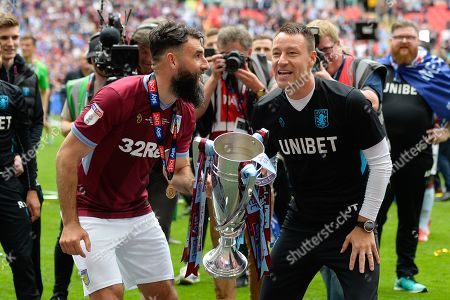 Aston Villa midfielder Mile Jedinak (15) holds the cup with Aston Villa assistant manager John Terry during the EFL Sky Bet Championship play off final match between Aston Villa and Derby County at Wembley Stadium, London
