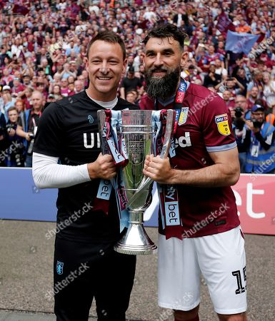 Aston Villa assistant head coach  John Terry and  Mile Jedinak with the winners trophy