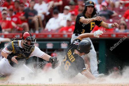 Adam Frazier, Tucker Barnhart. Pittsburgh Pirates' Adam Frazier (26) scores against Cincinnati Reds catcher Tucker Barnhart, left, on a two-run double by Bryan Reynolds off relief pitcher David Hernandez in the eighth inning during the first baseball game of a doubleheader, in Columbus