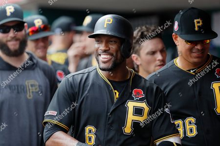 Pittsburgh Pirates' Starling Marte (6) celebrates in the dugout after hitting a two-run home run off Cincinnati Reds relief pitcher David Hernandez in the eighth inning during the first baseball game of a doubleheader, in Columbus