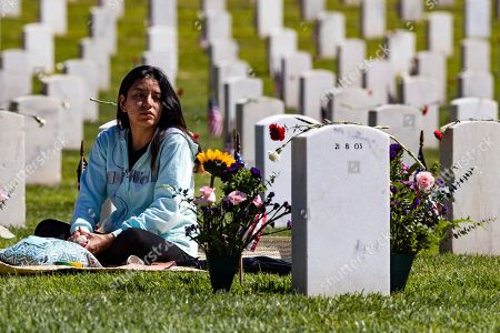 Stock Image of Carla Martinez sits beside the grave of her cousin Rodrigo, who died in Iraq in 2004, on Memorial Day at the Los Angeles National Cemetery in Los Angeles, California, USA, 27 May 2019.