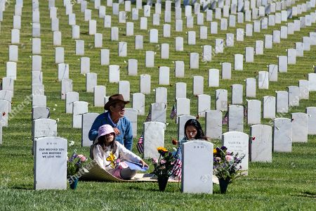 Stock Photo of Salomon Martinez (L) sits at the grave of his son Rodrigo, who died in Iraq in 2004, with Rodrigo's cousin Carla Martinez (R) on Memorial Day at the Los Angeles National Cemetery in Los Angeles, California, USA, 27 May 2019.