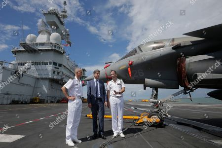 (L-R) Commander of French Task Force 473 Rear Admiral Olivier Lebas, French Ambassador Marc Abensour, and carrier commandant Captain Marc-Antoine de St Germaine pose for photographers next to a Rafale fighter jet on the flight deck of the French nuclear aircraft carrier Charles de Gaulle (R 91), berthed at the Changi Naval Base in Singapore, 28 May 2019. The carrier is the Marine Nationale's first nuclear powered vessel and is currently undertaking a five month deployment in the Mediterrenean sea and Indian ocean as part of French Task Force 473.