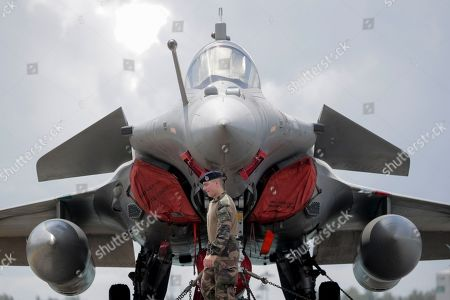 A French navy marine walks in front of a Rafale fighter jet on the flight deck of the French nuclear aircraft carrier Charles de Gaulle (R 91), berthed at the Changi Naval Base in Singapore, 28 May 2019. The carrier is the Marine Nationale's first nuclear powered vessel and is currently undertaking a five month deployment in the Mediterrenean sea and Indian ocean as part of French Task Force 473.