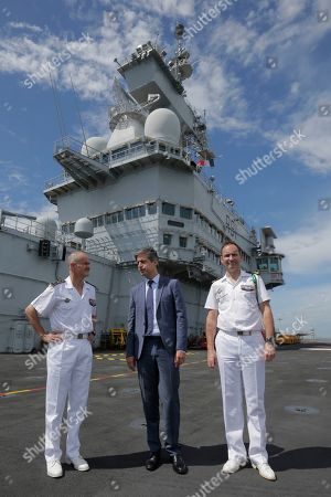 (L-R) Commander of French Task Force 473 rear admiral Olivier Lebas, French Ambassador Marc Abensour, and Carrier Commandant Captain Marc-Antoine de St Germaine pose for photographers in front of the superstructure of the French nuclear aircraft carrier Charles de Gaulle (R 91), berthed at the Changi Naval Base in Singapore, 28 May 2019. The carrier is the Marine Nationale's first nuclear powered vessel and is currently undertaking a five month deployment in the Mediterrenean sea and Indian ocean as part of French Task Force 473.