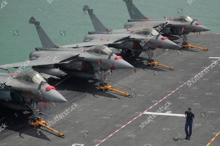 A French navy sailor walks past a row of Rafale fighter jets on the flight deck of the French nuclear aircraft carrier Charles de Gaulle (R 91), berthed at the Changi Naval Base in Singapore, 28 May 2019. The carrier is the Marine Nationale's first nuclear powered vessel and is currently undertaking a five month deployment in the Mediterrenean sea and Indian ocean as part of French Task Force 473.