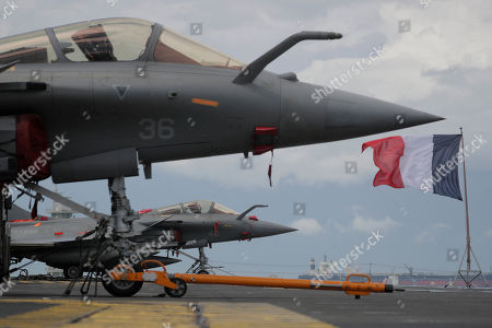 The French flag flutters behind two French Navy Rafale fighter jets on the flight deck of the French nuclear aircraft carrier Charles de Gaulle (R 91), berthed at the Changi Naval Base in Singapore, 28 May 2019. The carrier is the Marine Nationale's first nuclear powered vessel and is currently undertaking a five month deployment in the Mediterrenean sea and Indian ocean as part of French Task Force 473.
