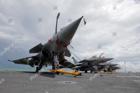 Stock Picture of A view of a row of French navy Rafale fighter jets on the flight deck of the French nuclear aircraft carrier Charles de Gaulle (R 91), berthed at the Changi Naval Base in Singapore, 28 May 2019. The carrier is the Marine Nationale's first nuclear powered vessel and is currently undertaking a five month deployment in the Mediterrenean sea and Indian ocean as part of French Task Force 473.