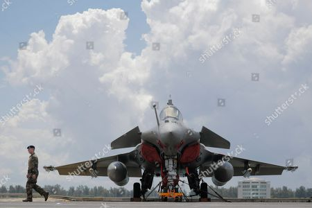 A French navy marine walks past a Rafale fighter jet on the flight deck of the French nuclear aircraft carrier Charles de Gaulle (R 91), berthed at the Changi Naval Base in Singapore, 28 May 2019. The carrier is the Marine Nationale's first nuclear powered vessel and is currently undertaking a five month deployment in the Mediterrenean sea and Indian ocean as part of French Task Force 473.