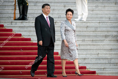 Xi Jinping, Peng Liyuan. Chinese President Xi Jinping, left, and his wife Peng Liyuan arrive for a welcome ceremony for Niger's President Mahamadou Issoufou at the Great Hall of the People in Beijing