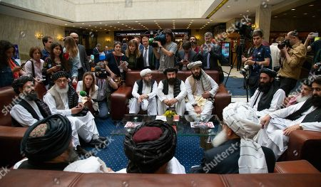 Mullah Abdul Ghani Baradar, the Taliban group's top political leader, left, Sher Mohammad Abbas Stanikzai, the Taliban's chief negotiator, second left, and other members of the Taliban delegation speak to reporters prior to their talks in Moscow, Russia, . Baradar and a team of 14 Taliban are headed to Moscow where they are scheduled to meet other Afghans including former President Hamid Karzai and some of the candidates in the presidential elections