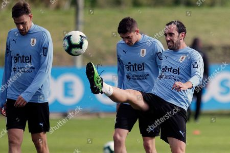 Uruguay's Diego Godin kicks the ball flanked by Sebastian Coates, left, and Diego Valverde during a training session on the outskirts of Montevideo, Uruguay, . Uruguay will face Panama in a friendly match on June 7
