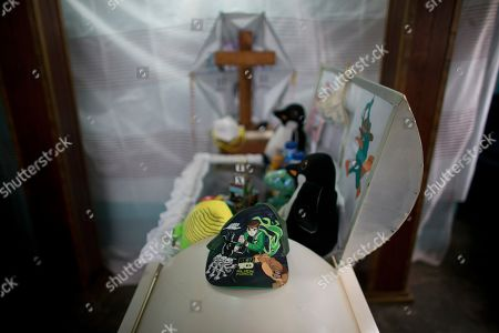 A cap belonging to 11-year-old Erick sits on the coffin that contains his remains, in his home in the Petare neighborhood in Caracas, Venezuela, . The family of the 11-year-old Venezuelan boy who died of cancer while waiting for a bone marrow transplant held an open-casket wake on Tuesday, giving visitors a chance to see him for the last time and wonder whether the death could have been avoided