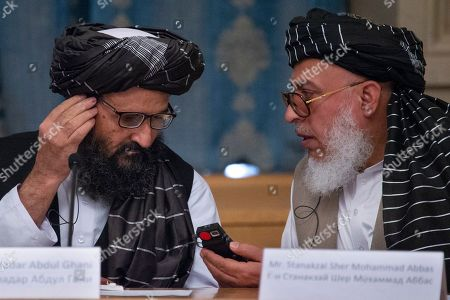 Mullah Abdul Ghani Baradar, the Taliban group's top political leader, left, and Sher Mohammad Abbas Stanikzai, the Taliban's chief negotiator, talk to each other during a meeting in Moscow, Russia, . Baradar and a team of 14 Taliban are headed to Moscow where they are scheduled to meet other Afghans including former President Hamid Karzai and some of the candidates in the presidential elections