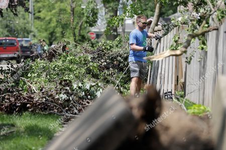 Stock Photo of Matt Roberts removes debris from around his house, in Pendleton, Ind., following a tornado the struck the night before. The severe storm damaged at least 75 homes in Pendleton