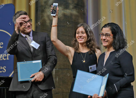 Associated Press Middle East editor Lee Keath, from left, joins AP's 2019 Pulitzer Prize winners for International Reporting, Nariman El-Mofty, Maggie Michael and Maad al-Zikry, who joins by El-Mofty's cellphone video, after they received their certificates at an awards luncheon at Columbia University, in New York. Al-Zikry was refused a visa to travel for the prize, awarded for a revelatory yearlong series detailing the atrocities of the war in Yemen, including theft of food aid, deployment of child soldiers and torture of prisoners