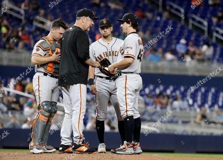 San Francisco Giants manager Bruce Bochy, second from left, talks with relief pitcher Derek Holland, right, during the sixth inning of a baseball game against the Miami Marlins, in Miami